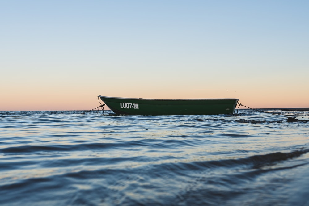 green boat on body of water during daytime