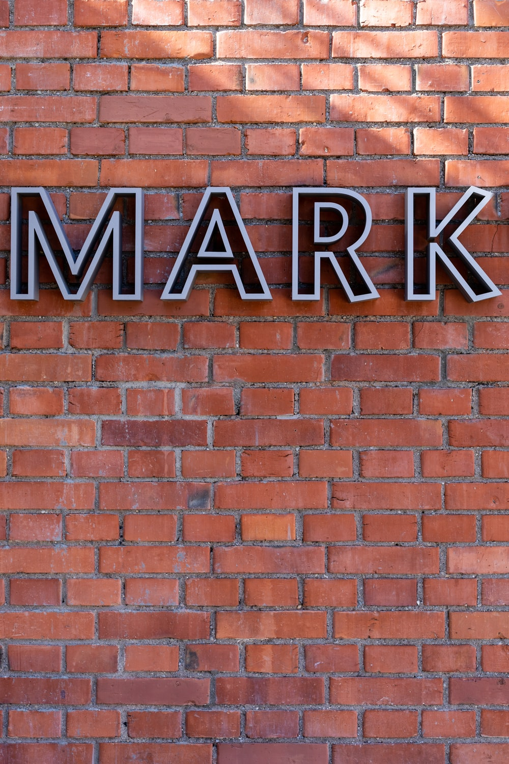 brown brick wall with black and white UNK sign