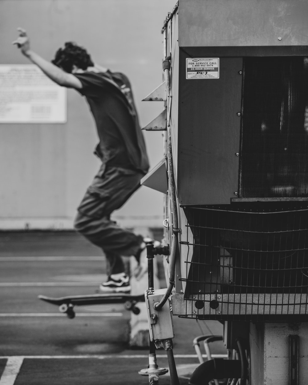 man in black t-shirt and pants riding on black skateboard in grayscale photography