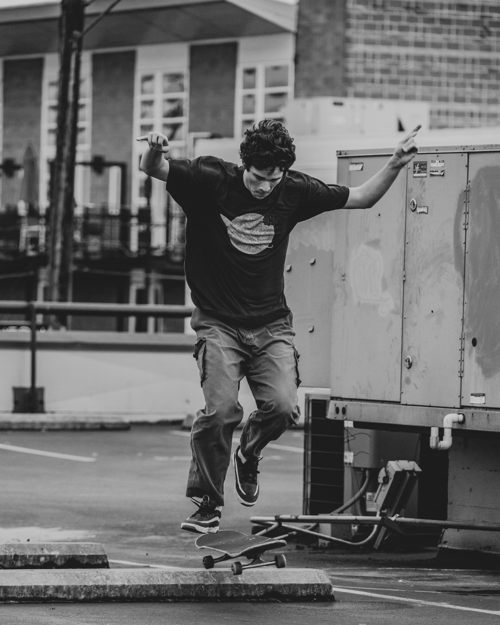 man in black t-shirt and brown pants jumping on skateboard in grayscale photography