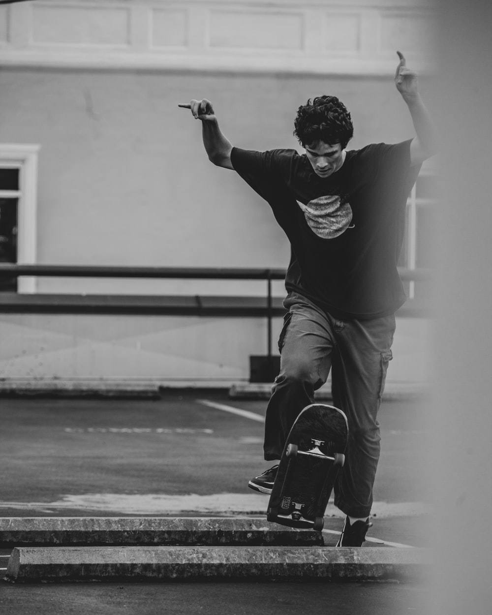 man in black long sleeve shirt and pants sitting on skateboard in grayscale photography