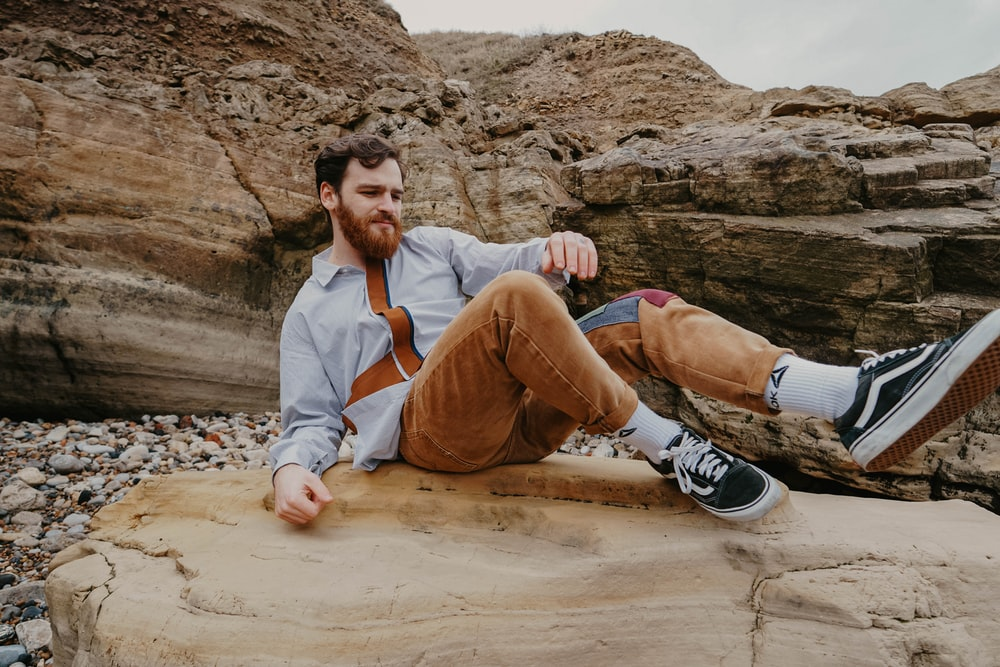 man in brown pants sitting on brown rock during daytime