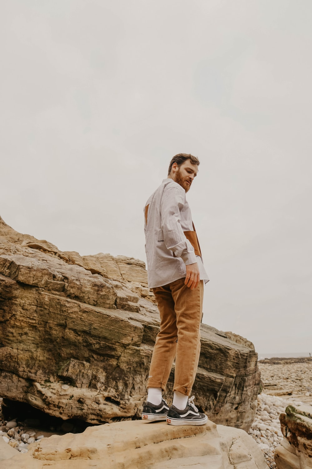 man in white dress shirt and brown pants standing on brown rock formation during daytime