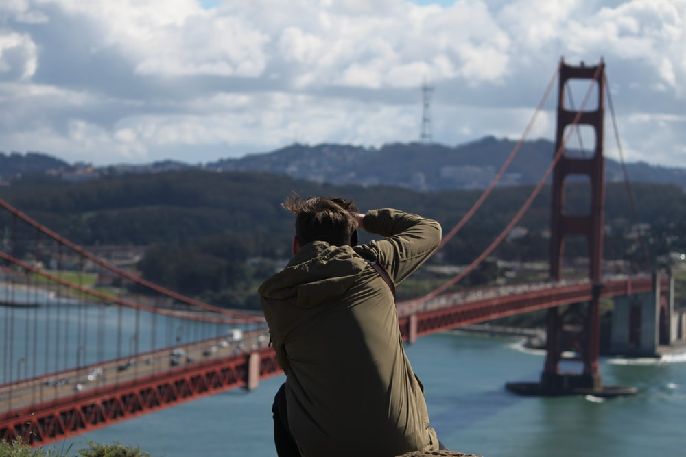 woman in brown jacket standing on bridge during daytime