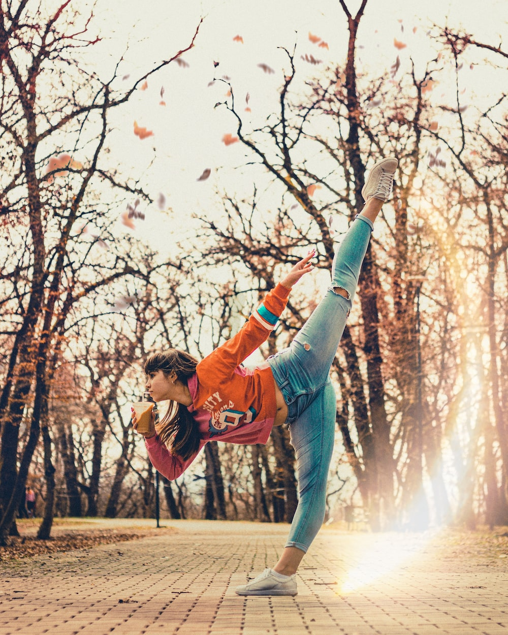 woman in red jacket and blue denim jeans jumping on tree branch
