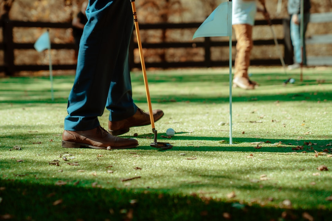 Putting on the green with a golf club and ball at a lawn party.