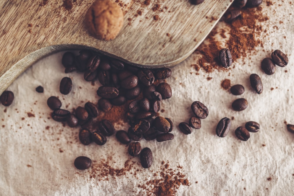 brown coffee beans on brown wooden chopping board