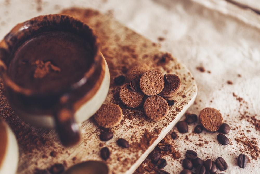 brown coffee beans on white ceramic mug