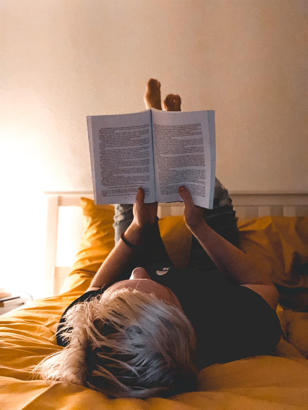 person reading book on bed