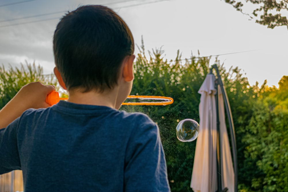 boy in blue shirt looking at the bubble