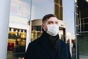 man in black robe wearing white face mask