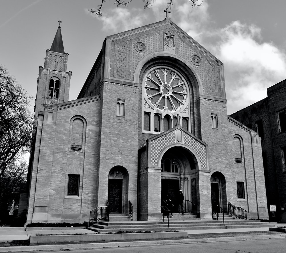 grayscale photo of church with cross on top