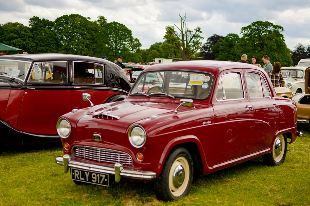 red vintage car on green grass field during daytime