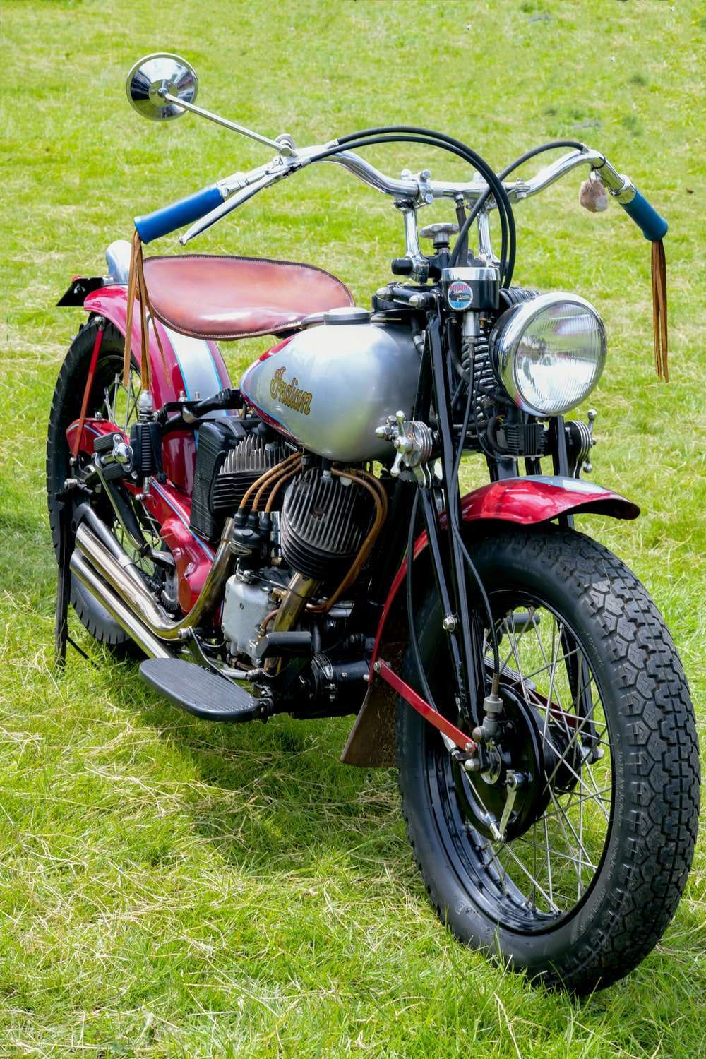 red and black motorcycle on green grass field during daytime