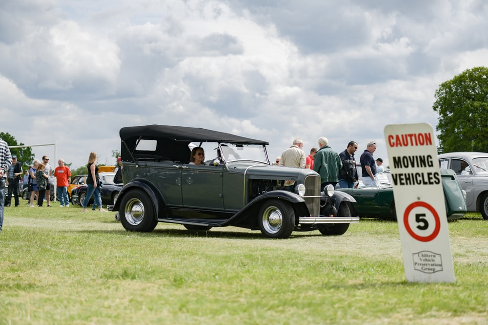 people riding on black vintage car on green grass field during daytime