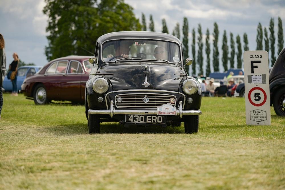 vintage black car on green grass field during daytime