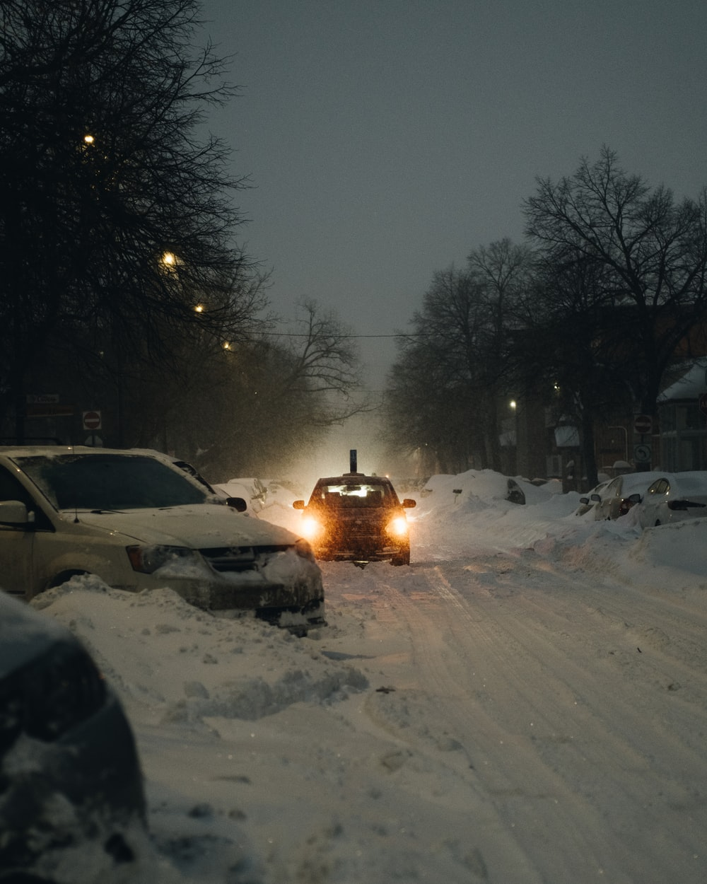 white car on snow covered road during night time