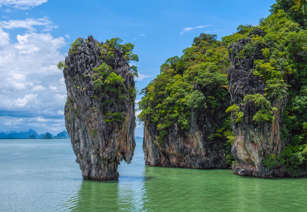 green and brown rock formation on blue sea under blue sky during daytime