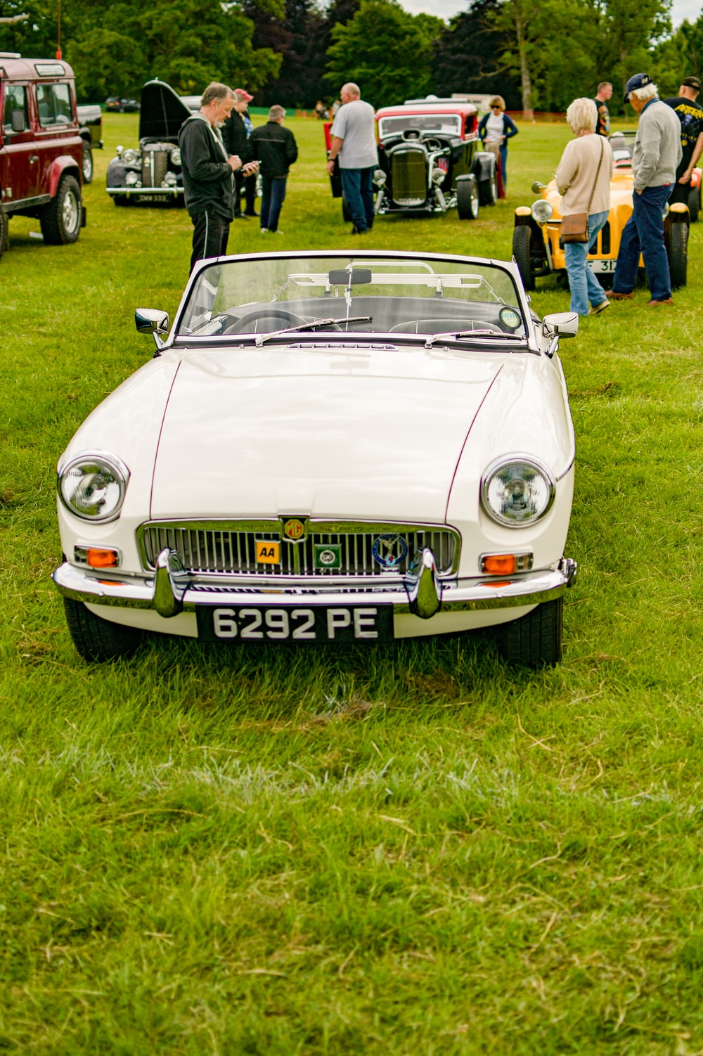 white mercedes benz convertible coupe on green grass field during daytime