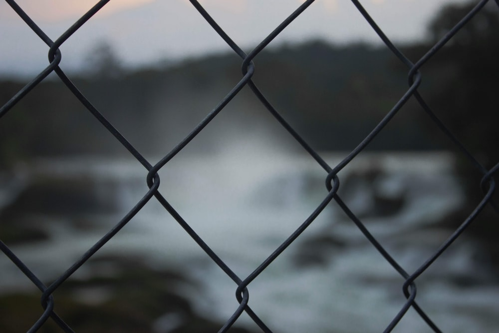 grey metal fence near body of water during daytime