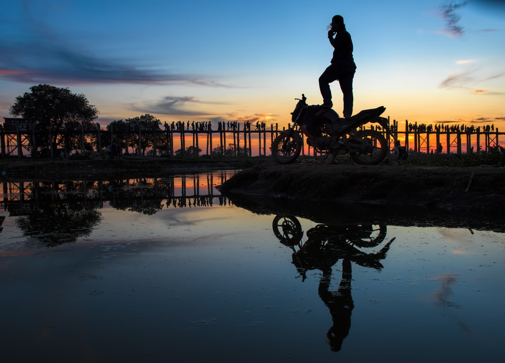 silhouette of man riding motorcycle on water during sunset