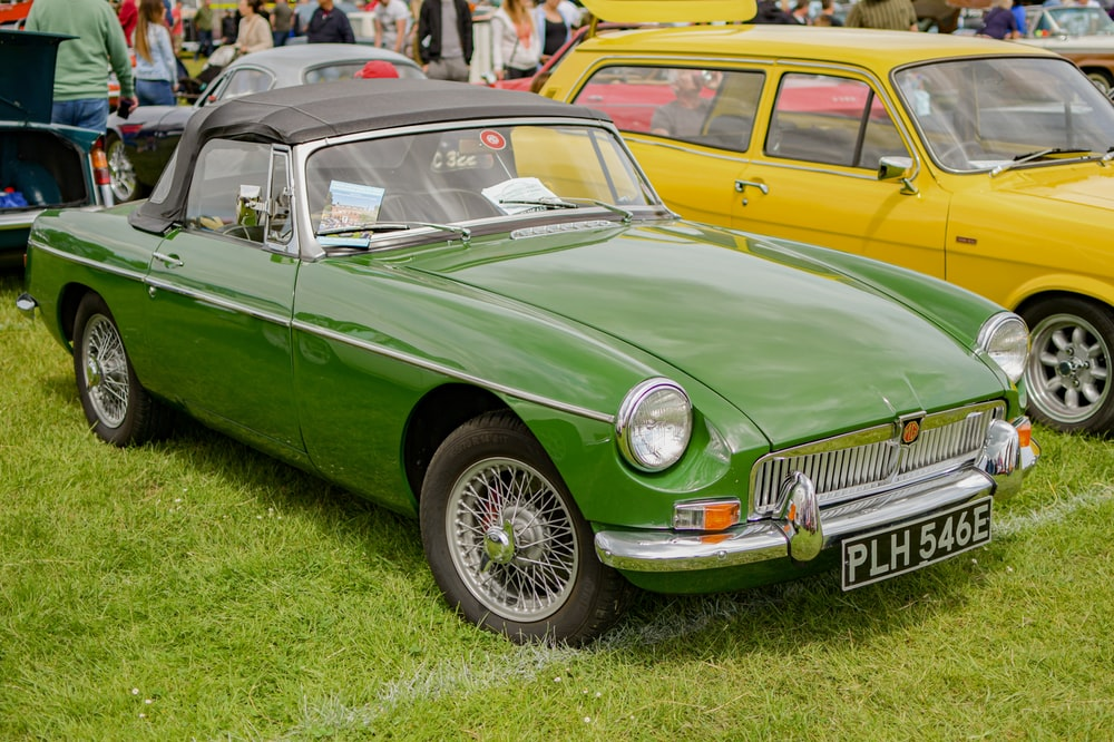 green classic car on green grass field during daytime