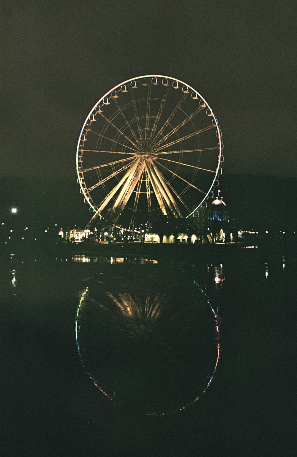 ferris wheel near body of water during night time