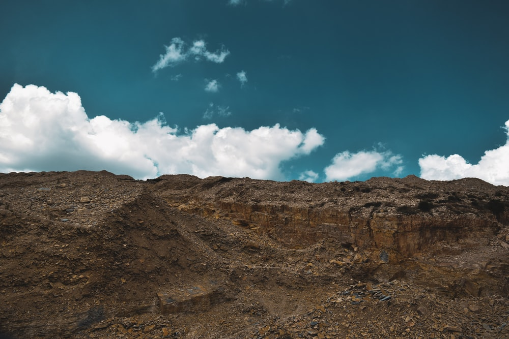 brown rocky mountain under blue sky and white clouds during daytime