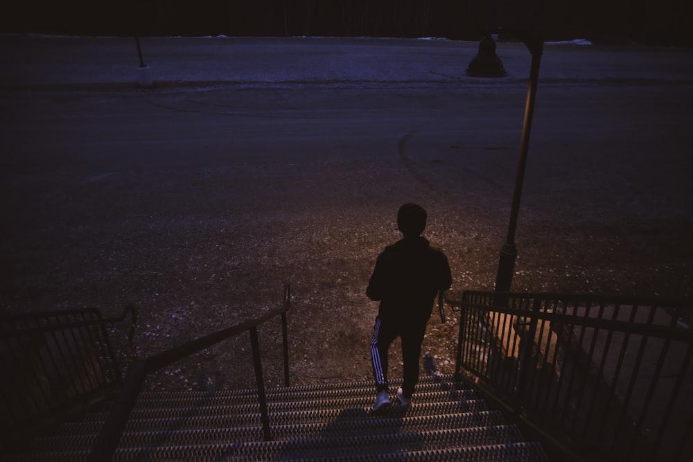 man in black jacket walking on gray sand during daytime
