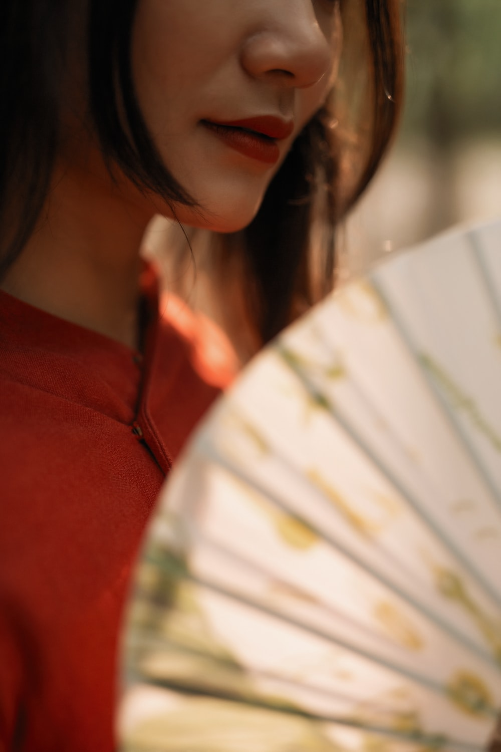 woman in red shirt holding white hand fan