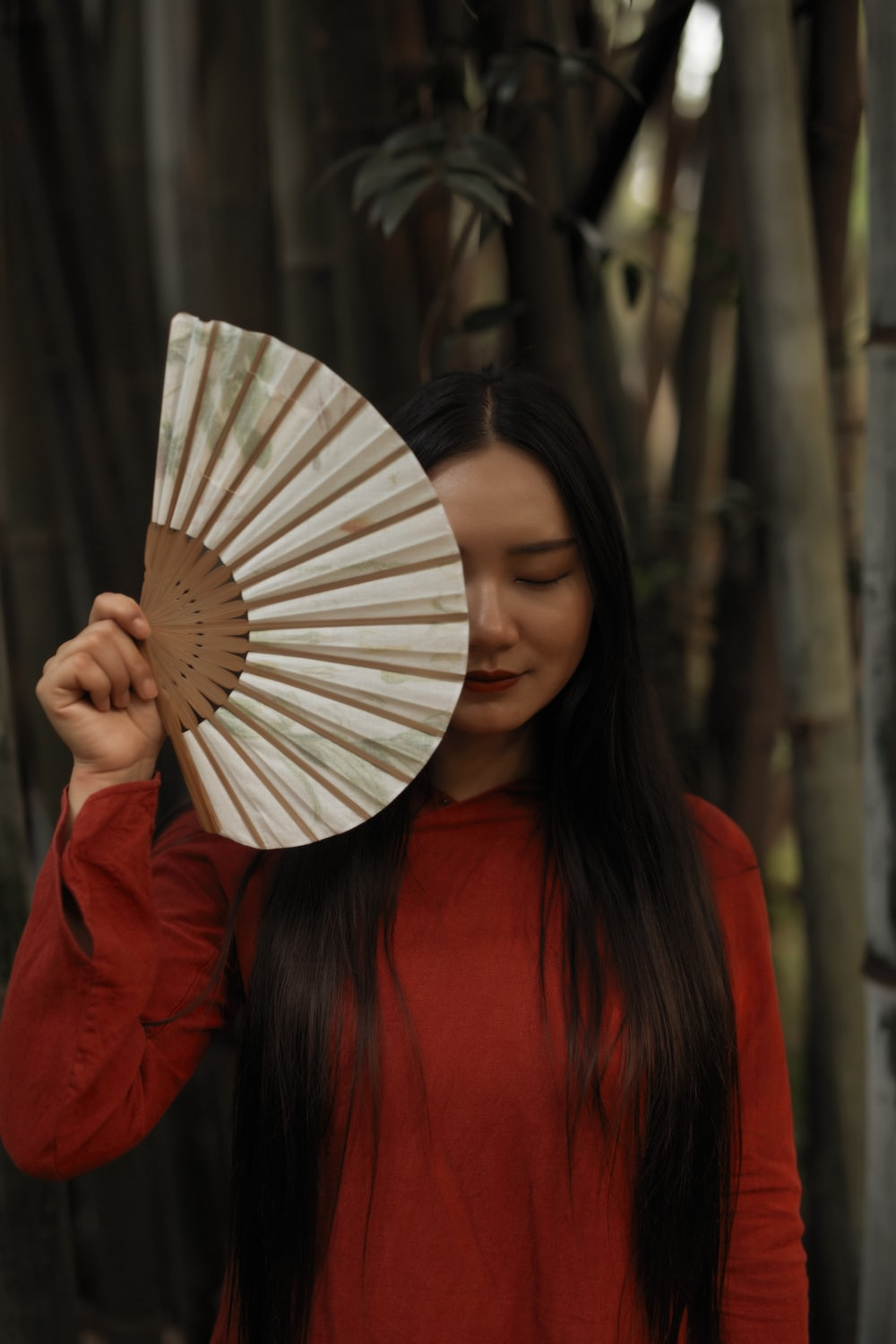 woman in red long sleeve shirt holding hand fan