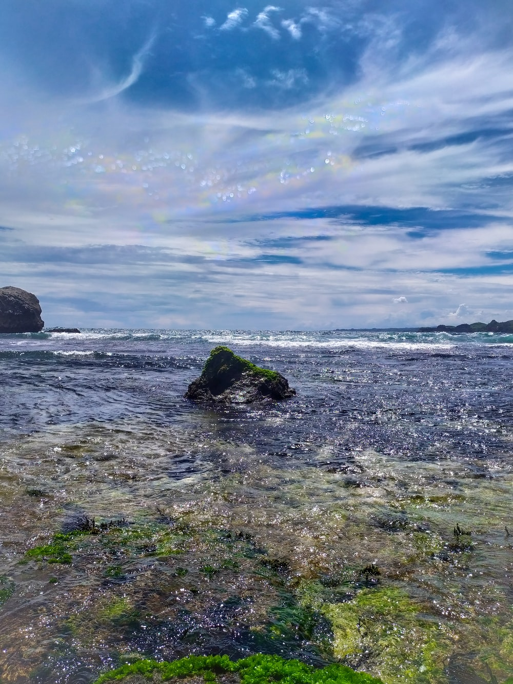 green and black rock formation on sea shore under blue and white sunny cloudy sky during