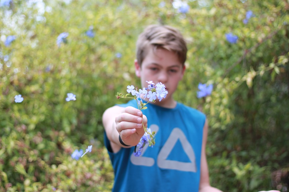 boy in blue crew neck t-shirt holding yellow and purple flower