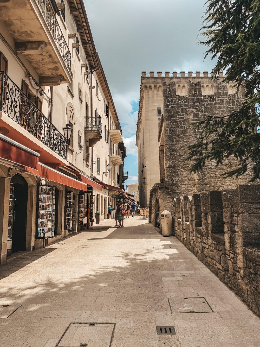 people walking on street between concrete buildings during daytime