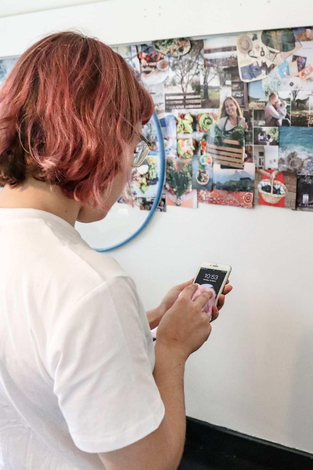woman in white shirt holding black smartphone