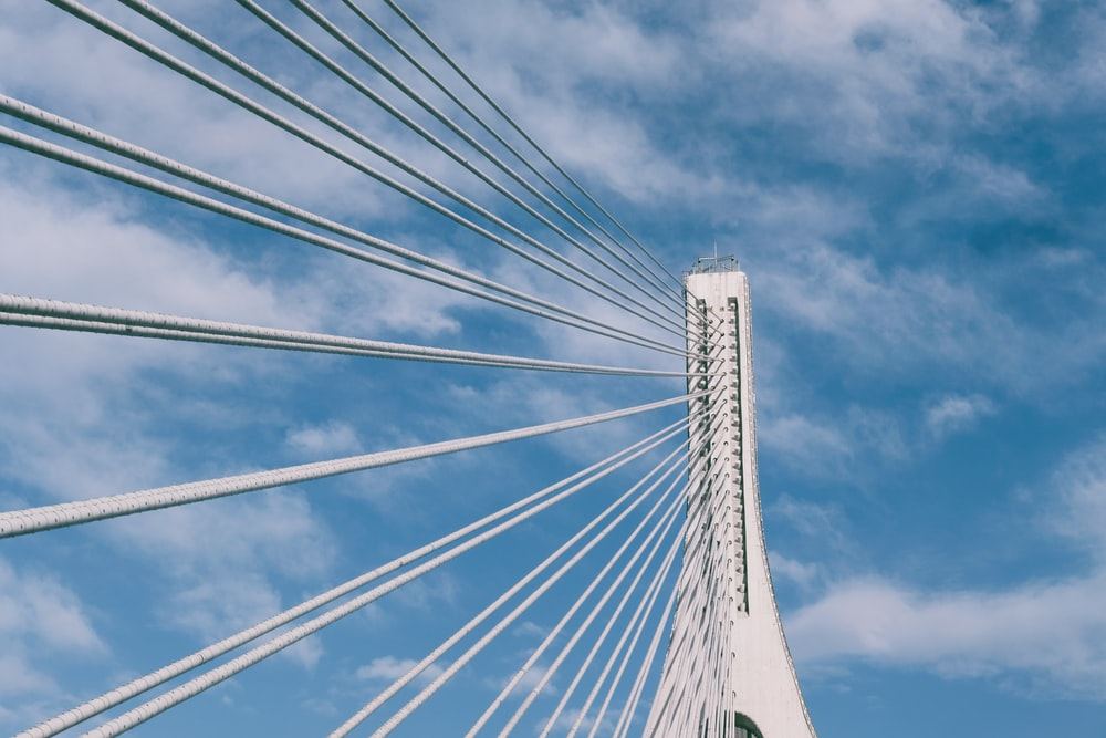 white and blue bridge under white clouds