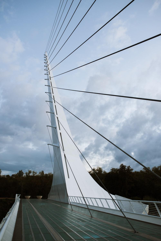 white metal bridge under white clouds during daytime
