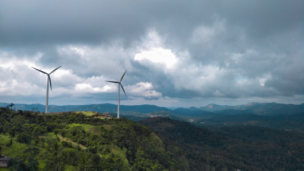 white wind turbine on green mountain under white clouds during daytime