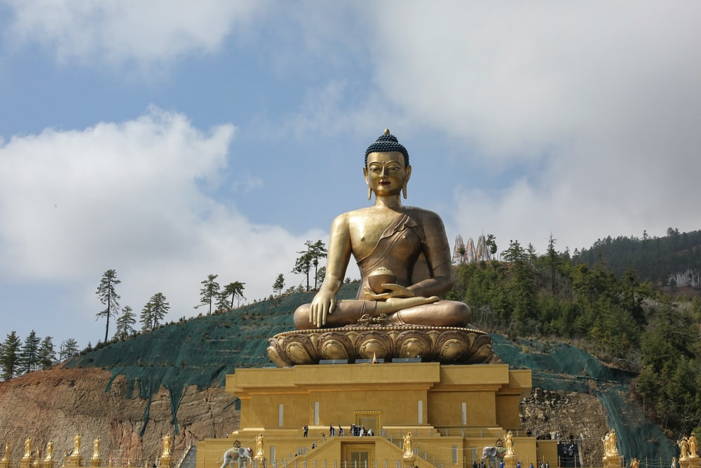 gold buddha statue under cloudy sky during daytime