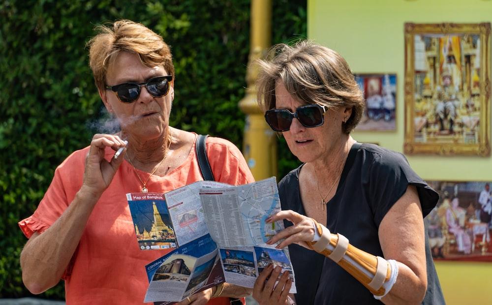 woman in orange tank top holding magazine
