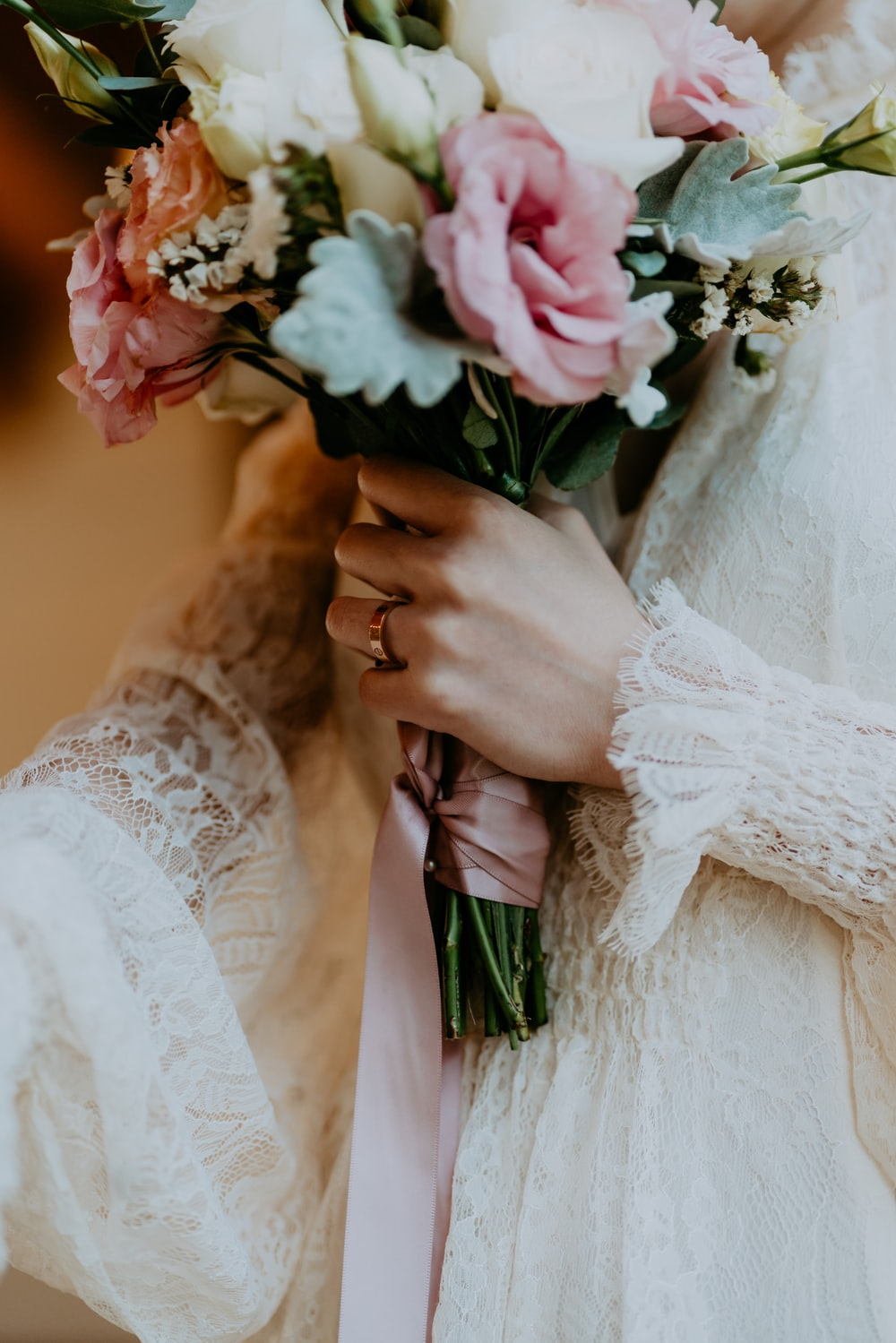 woman in white wedding dress holding white and pink flower bouquet
