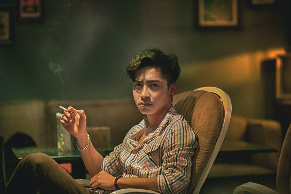 man in brown and white plaid button up shirt sitting on brown chair