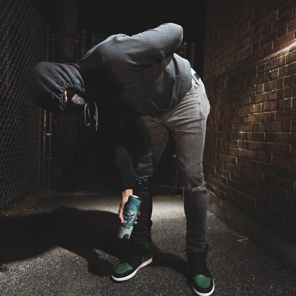 man in brown jacket and brown pants standing beside brick wall