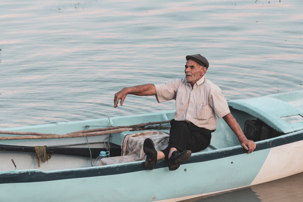man in white dress shirt and black pants sitting on white and brown boat during daytime