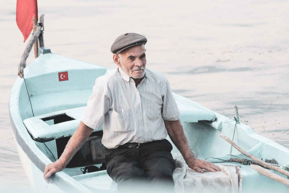 man in white button up shirt sitting on white boat during daytime