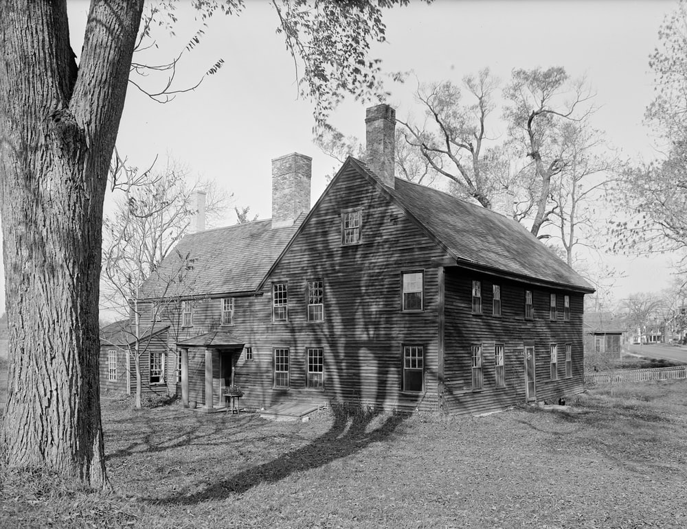 grayscale photo of wooden house near trees