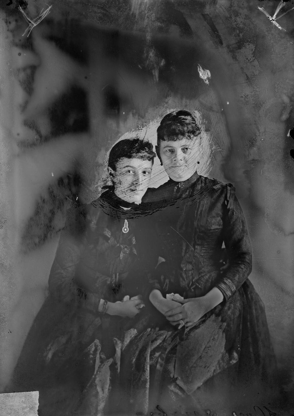 woman in black long sleeve dress carrying girl in black long sleeve dress