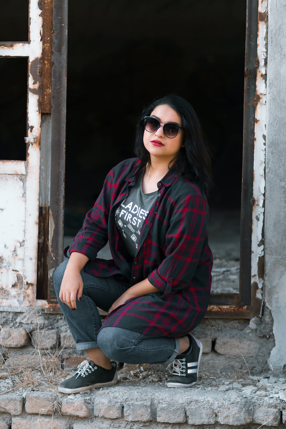 woman in red and black jacket and blue denim jeans wearing black sunglasses sitting on concrete