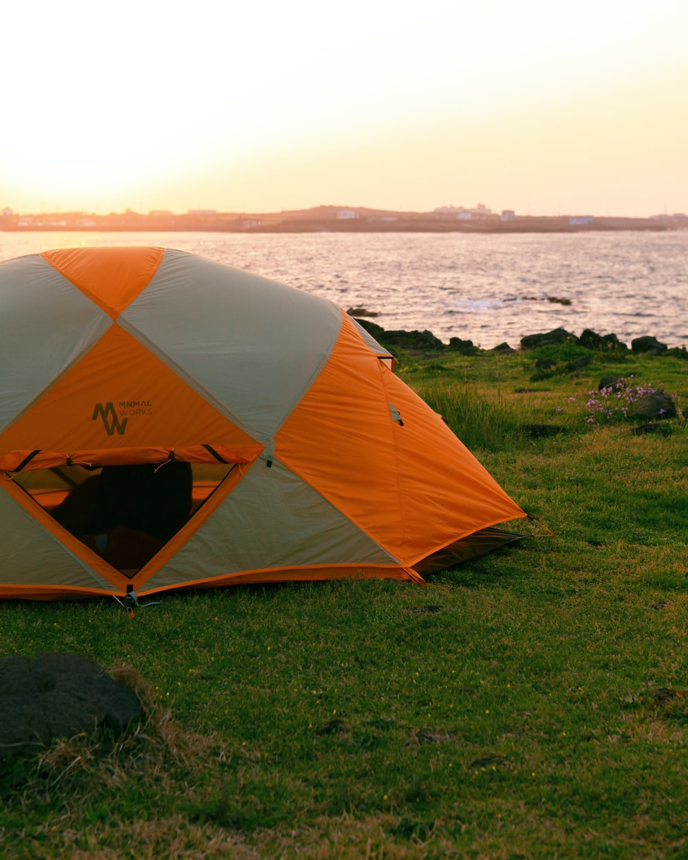 orange and gray dome tent on green grass field near body of water during daytime