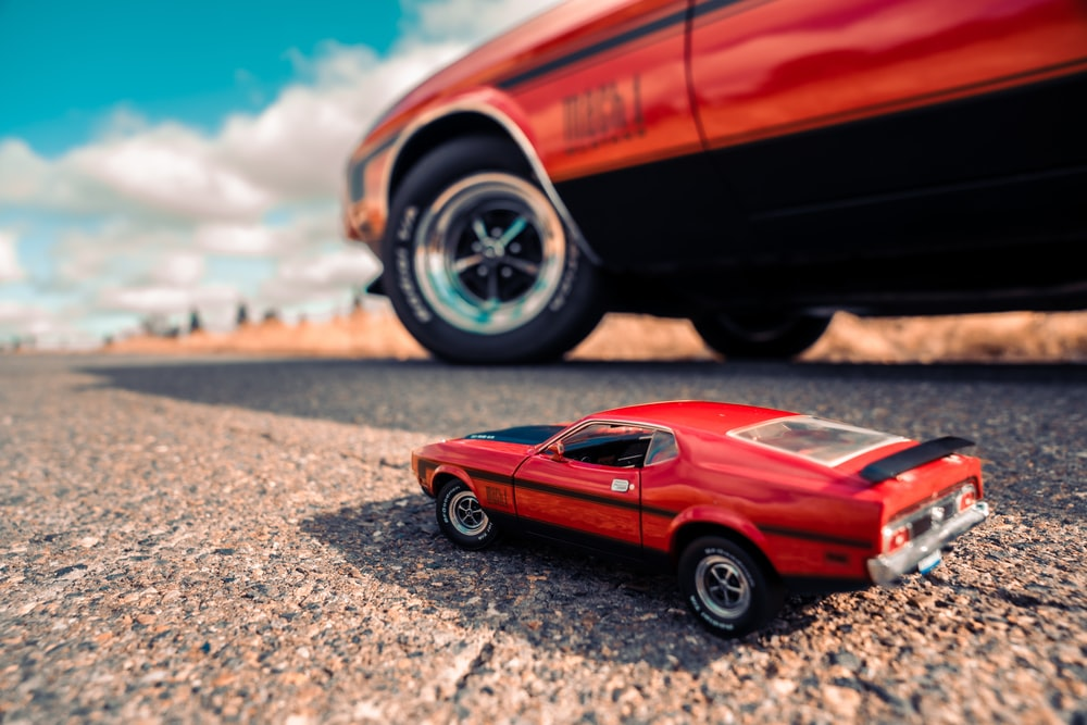 red coupe on gray asphalt road during daytime